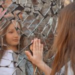 Girl Looking into Cracked Mirror